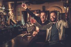Gamla vänner som har gyckel som håller ögonen på en fotbolllek på TV och dricker utkastöl på stångräknaren i bar Royaltyfria Bilder