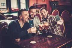 Gamla vänner som har gyckel som tar selfie och dricker utkastöl i bar Royaltyfri Fotografi