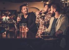 Gamla vänner som har roligt och dricker utkastöl på stångräknaren i bar arkivfoton