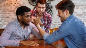 Gamla vänner som har utmaning för armbrottning i en bar royaltyfri foto