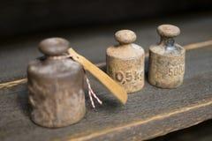 Gamla vikter på arbetsbänk - tappningkg-vikter på träbackgr Arkivfoto
