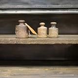 Gamla vikter på arbetsbänk - tappningkg-vikter på träbackgr Royaltyfria Bilder