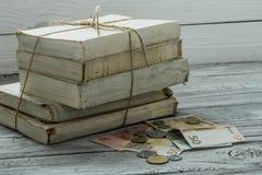 Gamla vita böcker med pengar och mynt på träbakgrund Arkivfoto