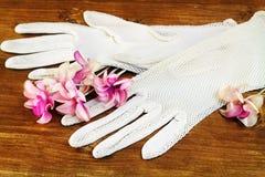 Gamla vita handskar och konstgjorda blommor Arkivbild