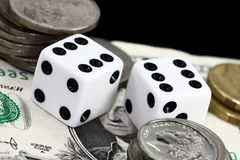 Gamling money. Two dice surrounded by piles of money Stock Image