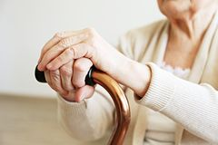 Gamlingkvinna med hälsoproblem som vilar hennes armar på att gå rottingen royaltyfria foton