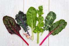 Gamma di verdura verde sana su una tavola bianca Immagini Stock