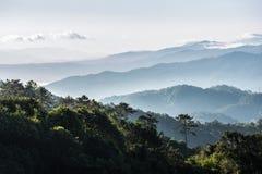 Gamma scenica delle montagne coperta da nebbia e da foschia Immagine Stock