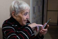 Gammal äldre kvinnapensionär som skriver på en smartphone Hj?lp royaltyfria bilder