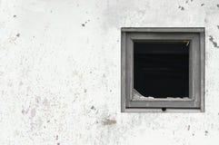 Gammal åldrig rostad för hyddakoja för grå vit målarfärg för vägg, bruten träram för fönsterexponeringsglas, målad riden ut smuts royaltyfri fotografi