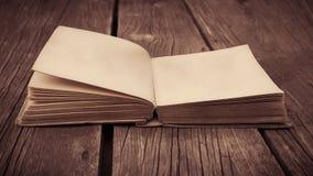 Gammal öppnad antik bok på trätabellen med den tomma sidan Arkivbilder