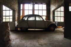 Gammal övergiven bil i ett glömt garage Arkivbild