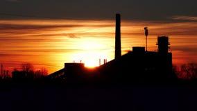 Gammal övergiven fabrik på bakgrunden av inställningssolen i vintertimelapsevideo stock video
