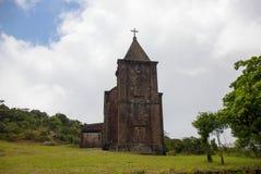 Gammal övergiven kyrka i grönt fält Medeltida fördärva i sommarlandskap Kristen tempel från den bruna stenen arkivfoto