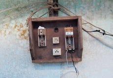 Gammal övergiven säkerhetsbrytare för elektrisk strömkrets på en grungevägg Royaltyfri Fotografi