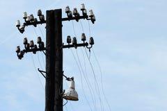 Gammal övergiven träelektrisk pylon med isolatorer och trådar royaltyfri bild