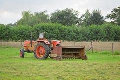 Gammal övergiven traktor med den rostiga hödrejaren i äng Fotografering för Bildbyråer