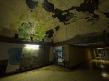 Gammal övergiven underjordisk tunnel, väggar med skalning av målarfärg och av murbruk arkivbilder