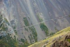 Gammal övergiven väg längs en brant backe med stenig stenras royaltyfri fotografi
