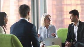 Gammal affärskvinna som talar till olika partners på internationella affärsförhandlingar
