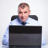 Gammal affärsman som arbetar på bärbara datorn royaltyfri bild
