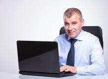 Gammal affärsman som arbetar på bärbara datorn royaltyfria foton