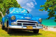 Gammal amerikansk bil på en strand i Kuba Arkivfoto