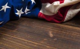 Gammal amerikanska flaggan på träplankabakgrund arkivfoton