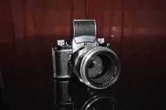 Gammal analog manuell tappningtyskSLR kamera för film för mm 35 på den svarta bakgrunden med den gamla tyska stående linsen Fotografering för Bildbyråer