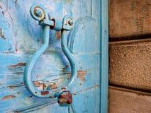 Gammal antikvitetblåttdörr med järnknackaren royaltyfria foton