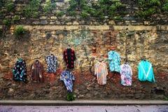Gammal använd kläder på väggen, gatuförsäljare, använda skjortor som dekoreras med kläder royaltyfri bild