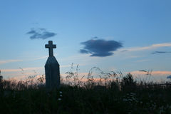 Gammal arg gravstenkontur på solnedgången i en kyrkogård Royaltyfri Bild