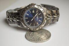 Gammal armbandsur- och silverdollar Fotografering för Bildbyråer