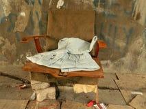 Gammal armstol med tegelstenar och gamla kläder royaltyfri bild