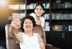 Gammal asiatisk kvinna som använder smartphonen för att ta selfie med hennes gran royaltyfri bild