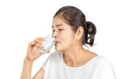 Gammal asiatisk kvinna som totalt dricker av vatten för hälsa royaltyfria bilder