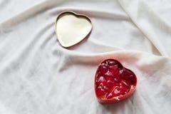 Gammal ask i hjärtaform på vit bakgrund, på den vita torkduken, i röda söta gelébönor för ask, dag för valentin` s, dag för kvinn Royaltyfri Fotografi