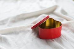 Gammal ask i hjärtaform på vit bakgrund, på den vita torkduken, i röda söta gelébönor för ask, dag för valentin` s, dag för kvinn Royaltyfria Foton