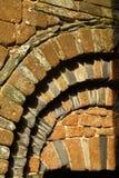 Gammal attraktiv tegelsten och kritiserar detaljen i en ärke- vägg Royaltyfri Fotografi
