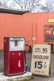 Gammal auto bensinstation som annonserar för billig bensin, arkivbild