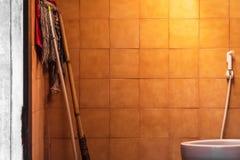 Gammal badrumbakgrund med rengörande utrustning Smutsigt badrum royaltyfria bilder