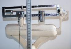Gammal badrumskala med att mäta stången för höjden och vikten Arkivfoton