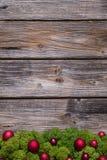 Gammal bakgrund av trä med röda xmas-bollar och mossa fotografering för bildbyråer