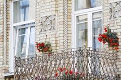 Gammal balkong av tegelstenhuset med blommor Arkivbilder