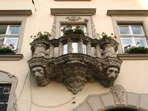 Gammal balkong med huvuden av lejon arkivfoto