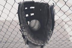 Gammal baseball i handske med dugoutstaketet Arkivfoton