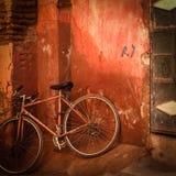 Gammal bicylce framme av den grungy röda väggen royaltyfri foto