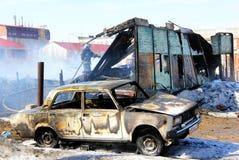 Gammal bil nära trähuset efter en brand Royaltyfri Bild