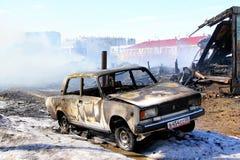 Gammal bil nära trähuset efter en brand Royaltyfria Foton
