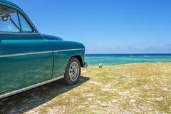 Gammal bil på en strand royaltyfria foton